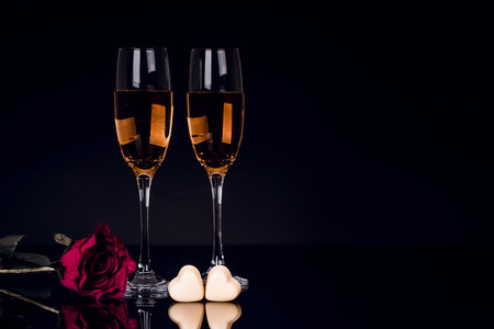 Two glasses of champagne, rose and two heart shape chocolates on black background with lights in the background. Love, Valentines day concept Stock Photo