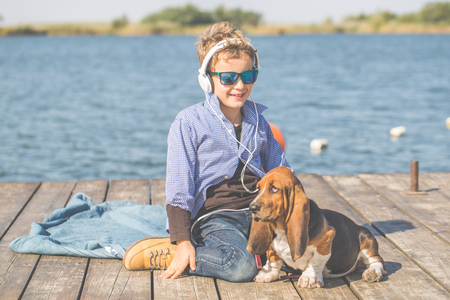 Little cute boy is sitting by the river with his dog. They enjoy together on a beautiful sunny day. Boy playing with his puppy. Growing up, love for animals - dogs, free time, travel, vacation. Copy space Stock Photo