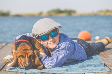Little cute boy with a cap lying by the river with his dog. They enjoy together on a beautiful sunny day. Boy hugging his puppy Basset Hound. Growing up, love for animals - dogs, free time, travel, vacation Stock Photo