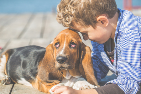 Happy little boy hugging his dog breed Basset Hound at the seashore against a blue sky close up. Best friends rest and have fun on vacation, play near the sea - Image Stock Photo