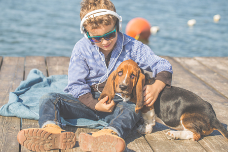 Little cute boy is sitting by the river with his dog. They enjoy together on a beautiful sunny day. Boy hugging his puppy Basset Hound. Growing up, love for animals - dogs, free time, travel, vacation.
