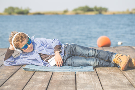 Little happy boy with sunglasses lying by the river and listening music via headphones on his smart phone.