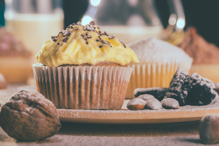 Closeup of a chocolate muffin cupcake with vanilla cream on a wooden board- Image