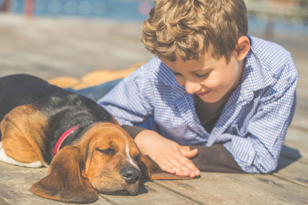 Little cute boy lying by the river with his dog. They enjoy together on a beautiful sunny day. Boy hugging his puppy. Growing up, love for animals - dogs, free time, travel, vacation. Copy space Stock Photo