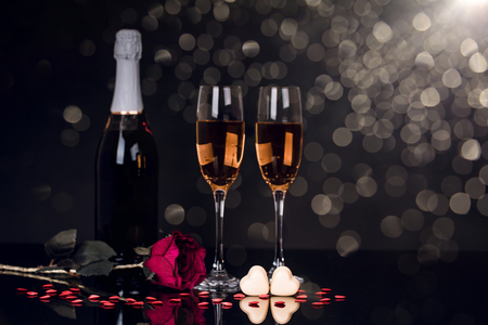 Two glasses of champagne, bottle, rose and two heart shape chocolates on black background. Love, Valentines day concept