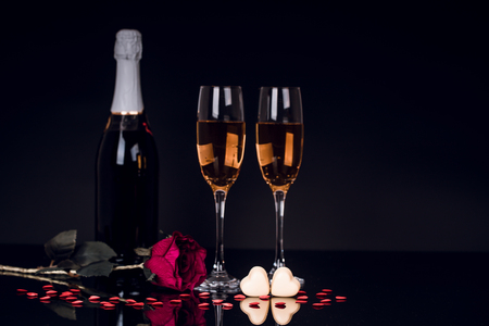 Champagne bottle with two wine glasses and  red rose on black background. Love, Valentines day concept. Copy Space.