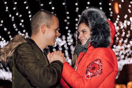 Attractive couple in love holding hands  and enjoying an intimate moment together, against the backdrop of city lights - Image
