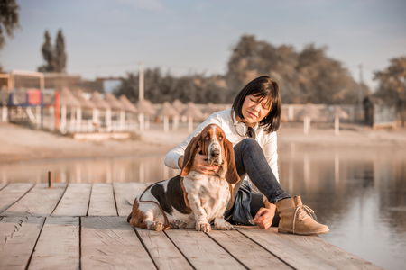 Portrait of beautiful young woman playing with dog by the river. Happy woman sitting on the wooden pier with her dog Basset Hound. Woman with puppy.