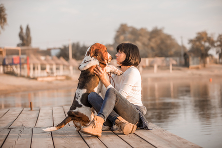 Young beautiful woman having great time with her dog Basset Hound while sitting next to river.