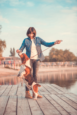 View of young woman holding hand up and playing with her dog Basset Hound standing on hind feet by the river Stock Photo