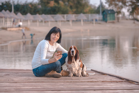Beautiful young woman chatting on smart phone while relaxing  with her dog on wooden pier by the river.