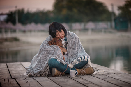 Portrait of beautiful young woman hugging her dog by the river. Happy woman with her dog Basset Hound covered with blanket sitting on the wooden pier in a sunset