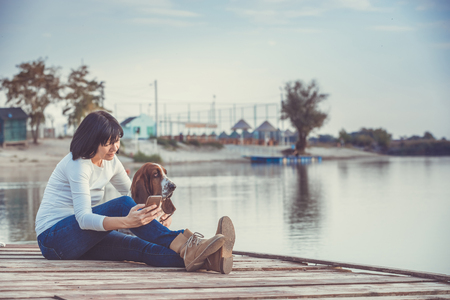 Portrait of beautiful young woman with her dog using mobile phone while sitting on wooden pier by the river. Stock Photo