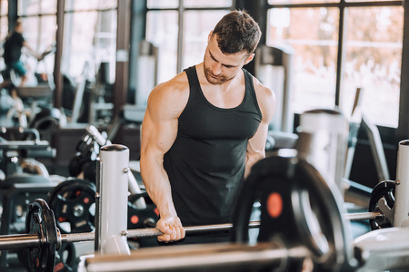 Muscular man working out in gym doing exercises with barbell at biceps, strong male torso abs - Image