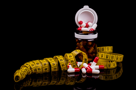 Closeup of a Glass bottle with diet pills and measuring tape isolated on black background. - Image