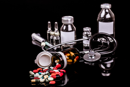 Medical capules, vials for injection with a syringe and ampules on black background - Image Stok Fotoğraf