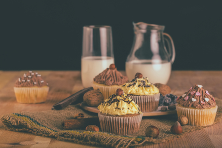 Homemade muffin cupcake with chocolate and vanilla cream on a wooden board with glass of milk in background - Image