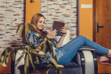 Young beautiful teenage girl sitting with tablet at home, learning. Smart girl with beautiful smile. - Image Фото со стока - 120196639