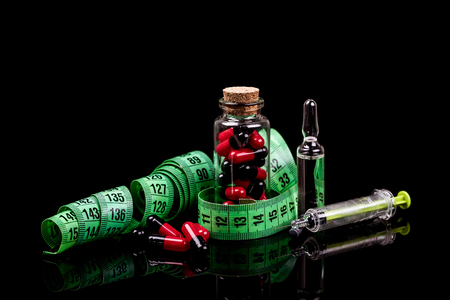 Closeup of a Glass bottle with diet pills and measuring tape isolated on black background. - Image Foto de archivo