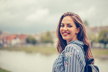 Portrait of a beautiful woman with a perfect smile outdoors - Image