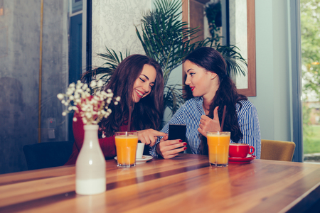 Two excited young girls using mobile phone while sitting in cafe and pointing finger - Image