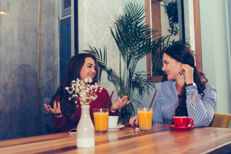 Happy female friends talking and drinking coffee while looking each other sitting in the table in a cafe. - Image