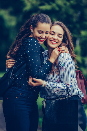 Close-up photo of two emotional happy woman friends hugging each other outdoors - Image 写真素材