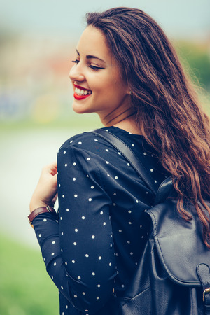 Portrait of a cheerful smiling girl with backpack  while walking outdoors.  - Image