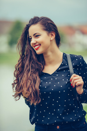 Close-up portrait of beautiful lady with trendy make-up spending vacation in Europe. Outdoor photo of smiling girl with dark-brown hair walking by the river in morning. - Imagee