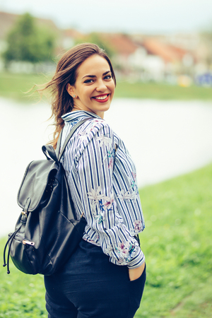Portrait of a beautiful smiling girl with backpack  while walking by the river.  - Image 写真素材