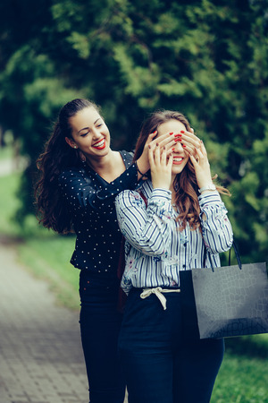 Girl make emotional surprise to her bestfriend covering eyes with hands. Happy and smiling best friends having emotional fun together in the park, after shopping. - Image