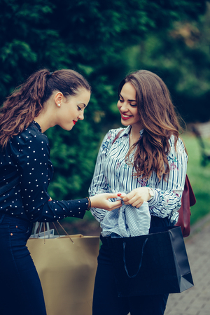 Two beautiful women walking in the park after shopping and sharing their new purchases with each other. Consumerism, shopping, lifestyle concept - Image