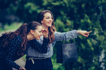 Two beautiful women having a relaxing conversation while walking in the park after shopping. Consumerism, shopping, lifestyle concept - Image 写真素材