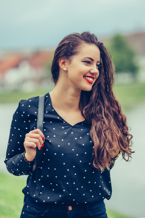 Close-up portrait of beautiful lady with trendy make-up spending vacation in Europe. Outdoor photo of smiling girl with dark-brown hair walking by the river in morning. - Image 写真素材