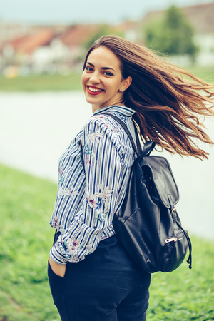 Portrait of a beautiful woman with a perfect smile and hair in motion outdoors - Image