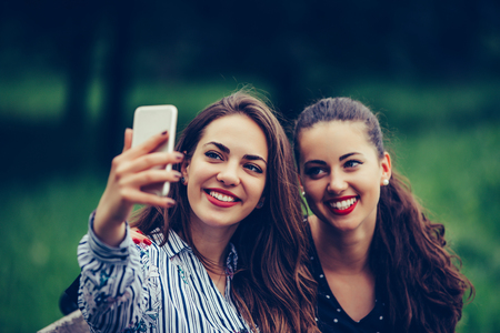 Image of young amazing women friends, students sitting in the park make selfie by mobile phone. - Image