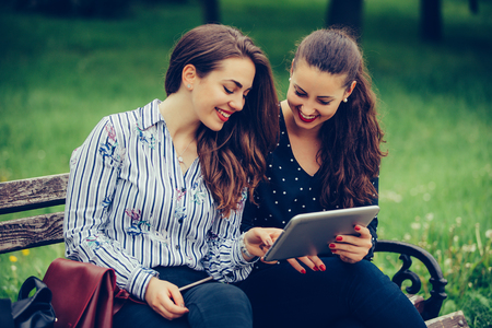 Two beautiful female friends using a digital tablet pc and laughing - Image 写真素材