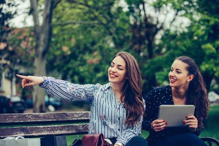 Two happy women holding digital tablet  pointing location standing in a park - Image