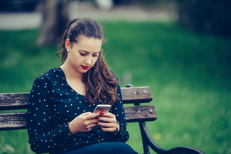 Girl texting on the smartphone sitting in a bench in a park - Image
