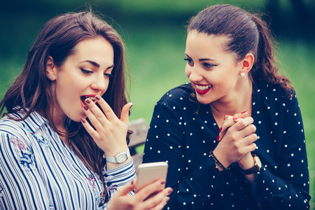 Euphoric female friends watching videos on a smartphone and pointing at screen surprised - Image 写真素材