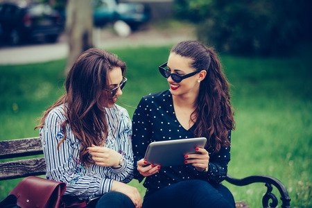 Two happy female friends laughing watching media content together in a digital tablet,  sitting on a bench in the park. - Image 写真素材