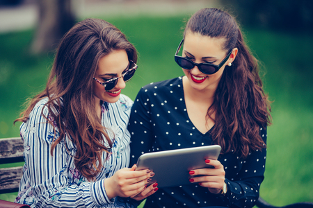 Two beautiful women laughing watching media content together in a digital tablet,  sitting on a bench in the park. - Image 写真素材