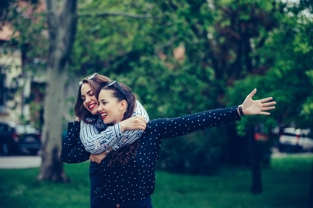 Outdoor shot of young woman carrying her female friend on her back. Two young woman having fun in the park. - Image 写真素材