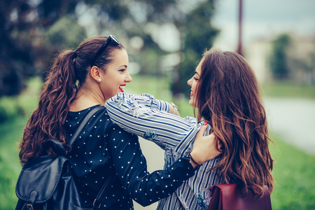 Back view of a two beautiful female friends hugging each other while walking through the park - Image