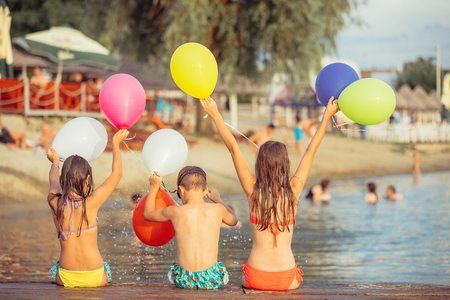 Happy kids holding color balloons while sitting on the beach. - Image 写真素材