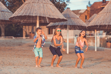Happy children having fun while jumping on the sandy beach. - Image