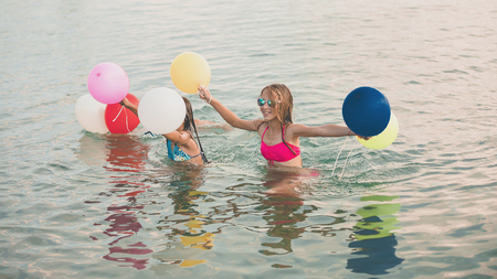 Happy little girls running together with balloons through the water at the beach - Image 写真素材
