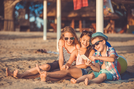 Portrait of positive children laughing watching funny video on smartphone on sandy beach together. - Image