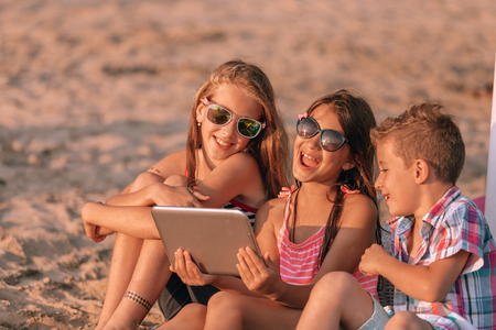 Portrait of positive children laughing watching funny video on digital tablet on sandy beach together. - Image