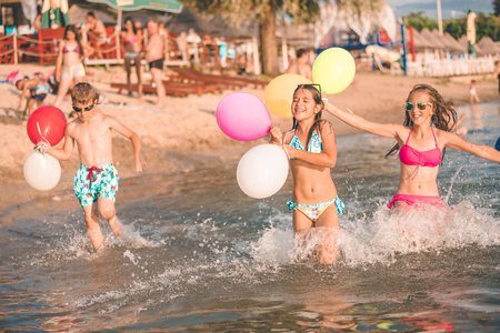 Happy children running together with balloons through the water at the beach - Image